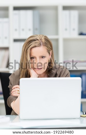 Businesswoman staring glumly at her laptop computer as she concentrates on information on the screen - stock photo