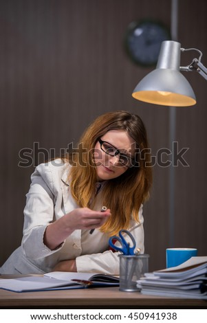 Businesswoman staying in the office for long hours - stock photo