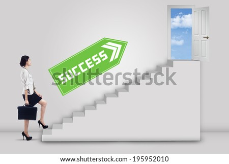 Businesswoman stepping up to the door of success with an arrow direction to the door - stock photo
