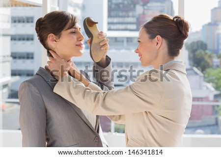 Businesswoman strangling another who is defending with her shoe in bright office - stock photo