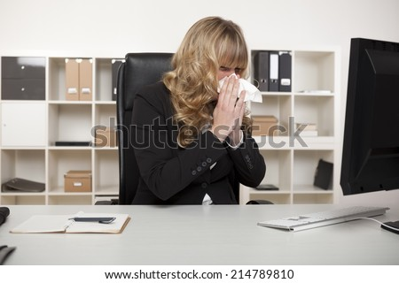 Businesswoman suffering from a cold or hay fever blowing her nose at her desk with a tissue as she continues reading the screen of her computer - stock photo
