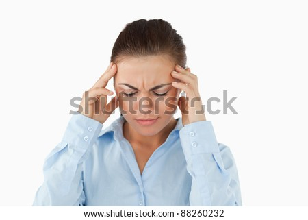 Businesswoman suffering from a headache against a white background