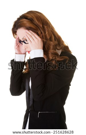 Businesswoman suffering from huge headache. - stock photo
