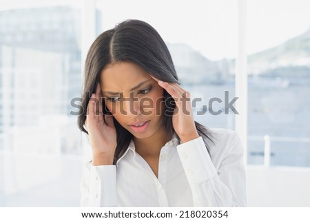 Businesswoman suffers a severe headache at work