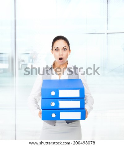 Businesswoman surprised scared, terrified hold stack folder, mouth open, young business woman concept of worried, shock lot of work in modern office - stock photo