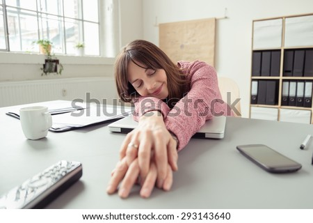 Businesswoman taking a relaxing break stretching her hands across the desk in front of her and laying down her head with a smile of contentment and eyes closed - stock photo