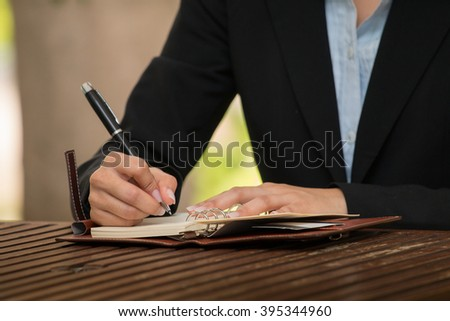 Businesswoman taking notes at hotel lobby.
