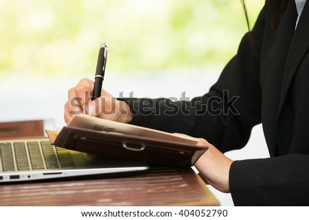 Businesswoman taking notes,working outdoor.