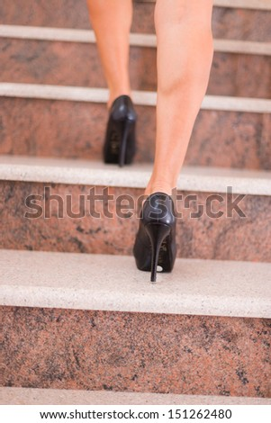 Businesswoman taking step to higher level on stairway - stock photo