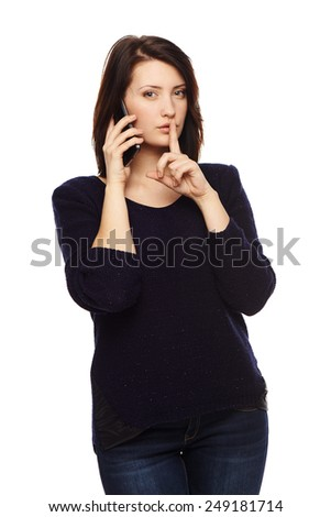 Businesswoman talking at cell phone and gesturing finger on lips, isolated over white background - stock photo