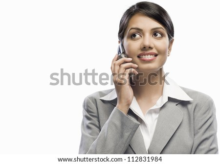 Businesswoman talking on a mobile phone against a white background - stock photo