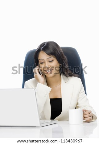 Businesswoman talking on a mobile phone and using a laptop