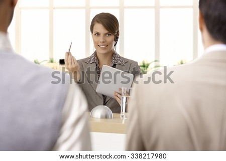 Businesswoman talking on formal speech at pulpit, colleagues listening. - stock photo
