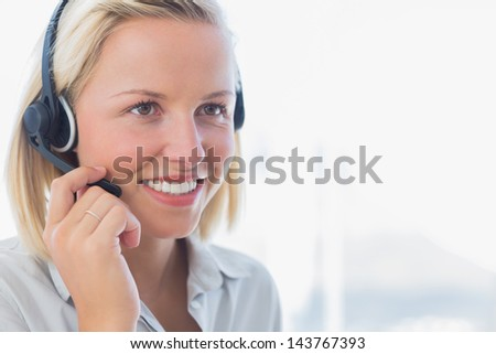 Businesswoman talking on headset and smiling