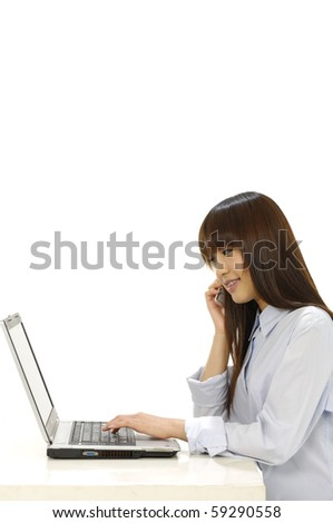 Businesswoman talking on mobile phone and using laptop