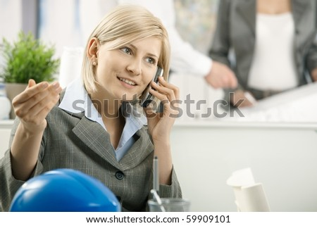 Businesswoman talking on mobile phone in office, gesturing.? - stock photo