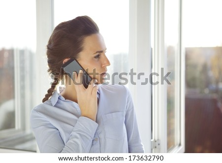 Businesswoman talking on mobile phone while standing by window and looking outside. Young caucasian female in office using phone. - stock photo
