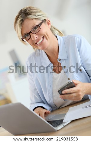 Businesswoman talking on phone in front of laptop - stock photo