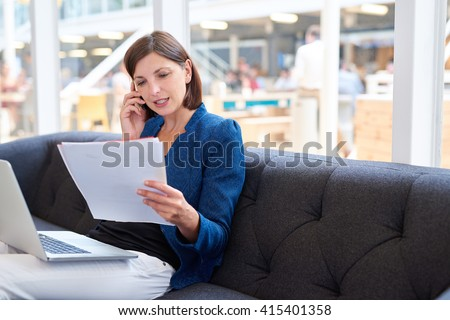 Businesswoman talking on phone while looking at paperwork - stock photo