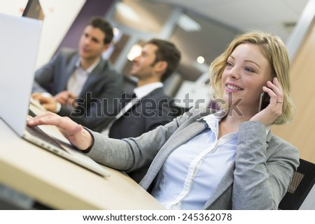 Businesswoman talking on the cell phone in modern office - stock photo