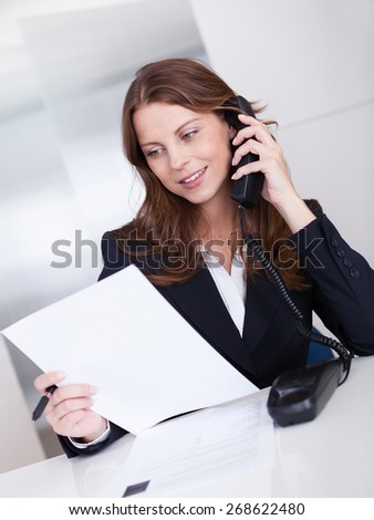 Businesswoman talking on the handset of a telephone as she sits at her desk working - stock photo