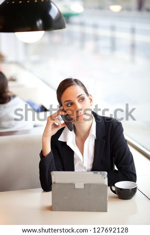 Businesswoman talking on the phone in a coffee shop