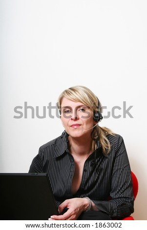 Businesswoman talking on the phone with a laptop and a headset