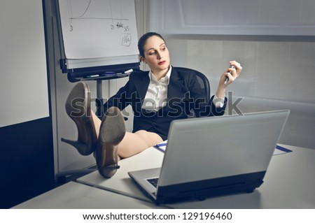 businesswoman talking on the phone with feet on the desk - stock photo