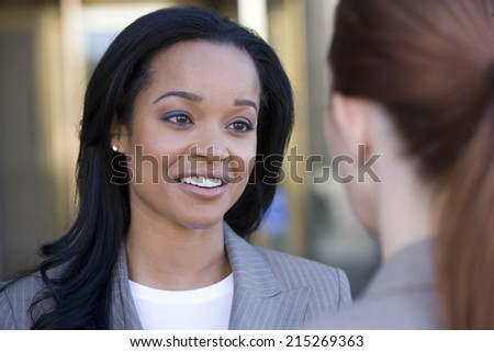 Businesswoman talking to colleague, smiling, close-up (differential focus)