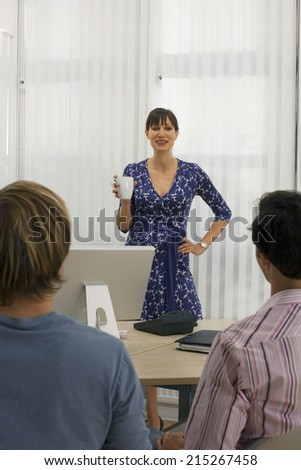 Businesswoman talking to male colleagues behind desk in office, woman holding mug, smiling
