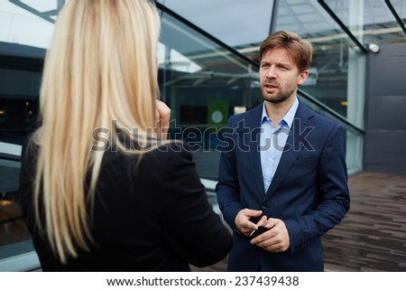 Businesswoman talking with her business partner standing near skyscraper office, confident businesspeople having serious conversation about the work, boss discussing with employee - stock photo