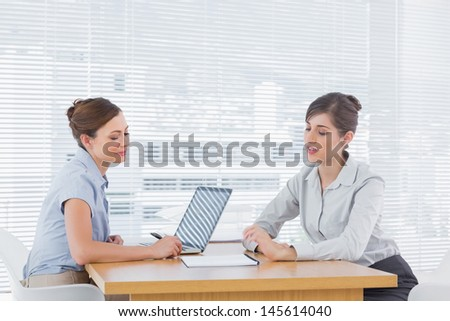 Businesswoman talking with interview candiate at desk in office - stock photo