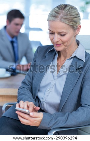 Businesswoman texting on her mobile phone with colleague in background in an office - stock photo