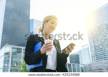 Businesswoman texting on smartphone - stock photo