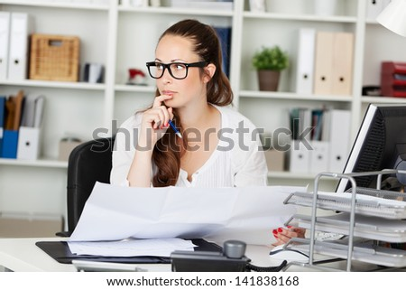 Businesswoman thinking and holding paper works on her table