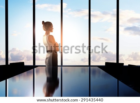 businesswoman thinking in office and looking to sky - stock photo