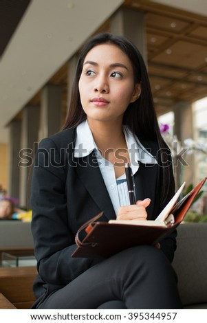 Businesswoman thinking with her notebook at hotel lobby.