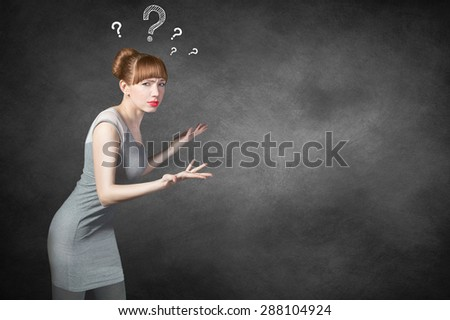 Businesswoman thinking with question marks on blackboard, black background. Female young adult university or college student looking scared sad lost wondering career choices. Question marks. No ideas - stock photo