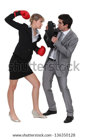 businesswoman threatening male colleague with boxing gloves - stock photo