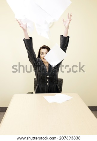 Businesswoman throwing papers into the air