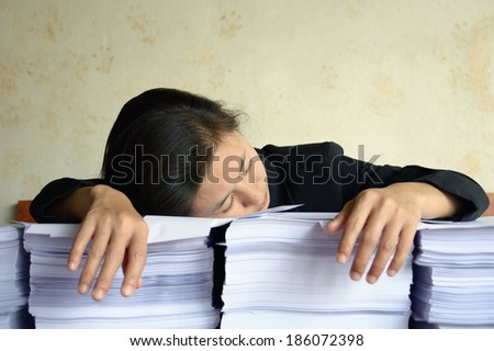 businesswoman tired and exhausted at a table on pile of papers