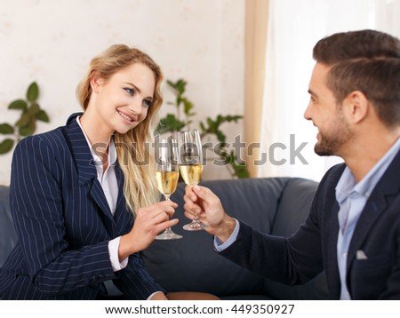 Businesswoman toast with businessman in office, teeth smile