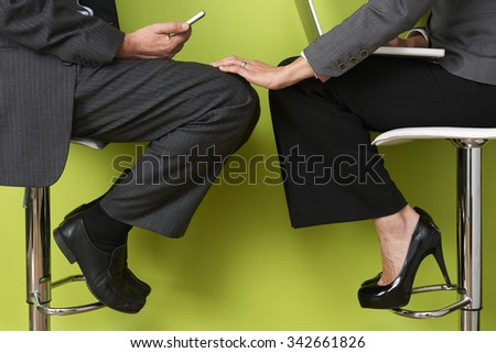 Businesswoman Touching Colleague's Leg