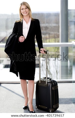Businesswoman traveling, standing beside her suitcase inside station or airport