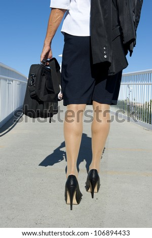 Businesswoman traveling with laptop, wearing white blouse, dark skirt and high heel shoes, isolated with blue sky as background and copy space.