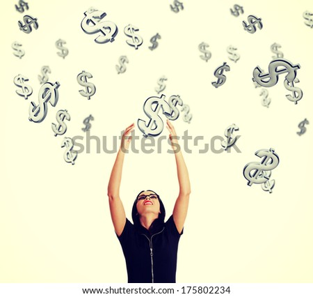 Businesswoman trying to catch falling down dollars. - stock photo