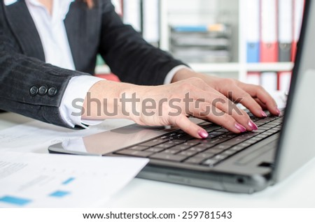 Businesswoman typing on a laptop at office