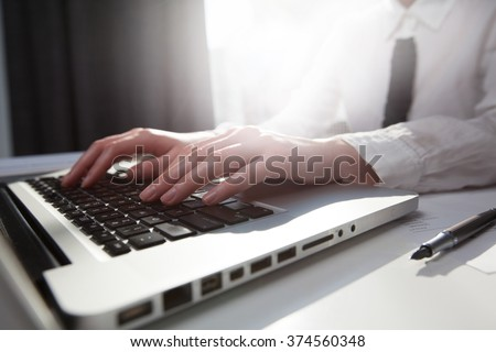 businesswoman typing on her laptop with sunflare - stock photo