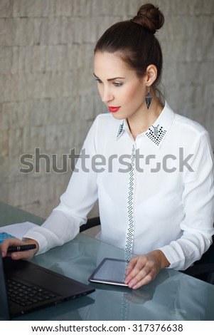 Businesswoman typing on laptop and using tablet, wireless tools in office - stock photo