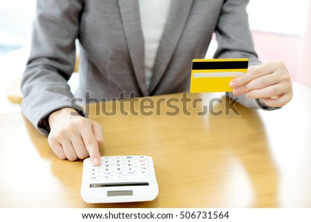 Businesswoman using a calculator to calculate his payment on credit card